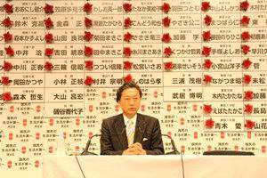 DPJ leader Senator Yukio Hatoyama, PhD in front of the election board with red rossetes on winning districts